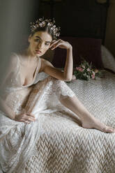 Young woman in wedding dress sitting on bed and looking sideways - ALBF01287