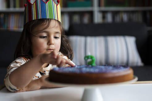 Portrait of little girl touching birthday cake - VABF03018