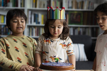 Portrait of little girl celebrating birthday with her older brothers at home - VABF03021