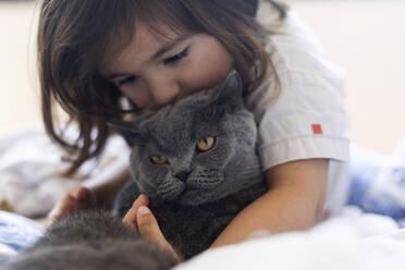 Little girl cuddling grey cat on bed - VABF03030
