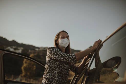Mid adult woman with protective mask at car - DMGF00101