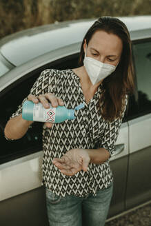Mid adult woman with protective mask using sanitizer out of the car - DMGF00104