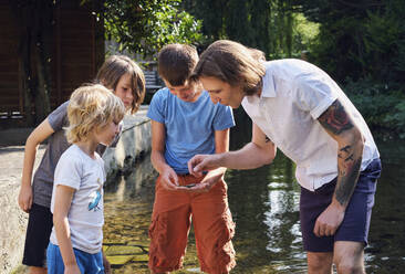 Father and children looking at something found in stream water - PWF00106