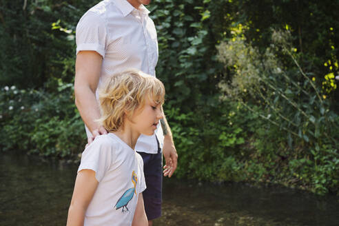Father and son walking in stream during sunny day at forest - PWF00112
