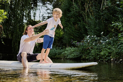 Happy father holding boy standing on paddleboard in stream at forest - PWF00118