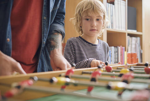 Father and son playing foosball at home - PWF00136