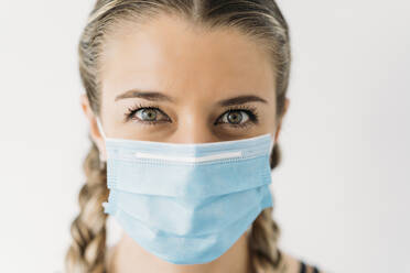 Portrait of beautiful young woman wearing face mask - MPPF00924