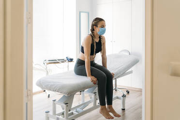 Sportswoman wearing face mask sitting on couch in examination room - MPPF00939