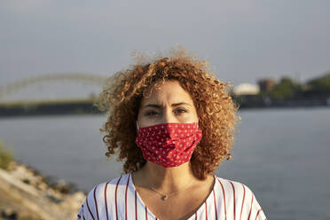 Woman with protective mask at riverside in the evening - MJFKF00347