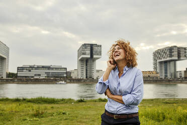 Businesswoman using smartphone at riverside in Cologne, Germany - MJFKF00350