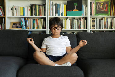 Boy sitting on couch meditating - VABF03046