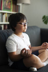 Boy sitting on couch meditating - VABF03049