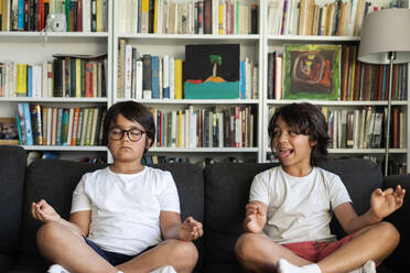 Boy sitting on couch meditating, his brother teasing him - VABF03052