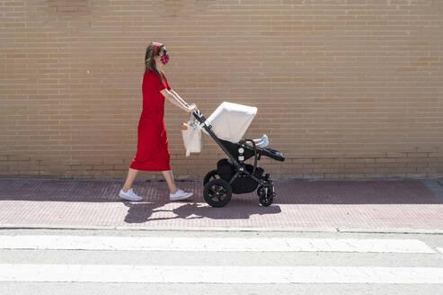 Mother wearing mask pushing son in baby carriage while walking on sidewalk - JCMF00797