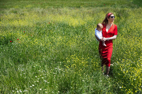Woman carrying baby son while walking on grassy land during sunny day - JCMF00803
