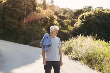 Senior man standing on road and looking sideways - AFVF06593