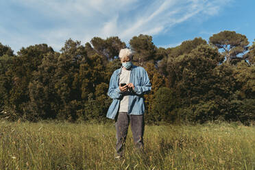 Senior man with mask using smartphone standing on meadow - AFVF06599