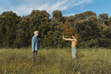 Woman and senior man with masks standing on meadow, holding safety distance - AFVF06602