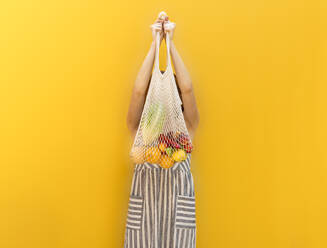 Young woman holding fruits in mesh bag while standing against yellow background - AFVF06607