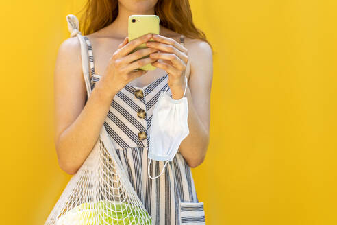 Young woman with bag mesh using smart phone against yellow background - AFVF06613