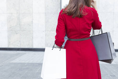 Young woman carrying shopping bags while standing on street in city - JPTF00521