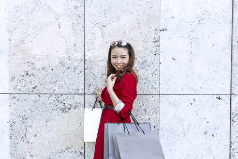 Smiling woman carrying shopping bags while standing by wall - JPTF00524