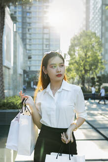 Confident young woman holding shopping bags while standing in city - JPTF00527