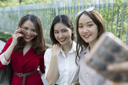 Smiling woman taking selfie with friends while standing in park - JPTF00539