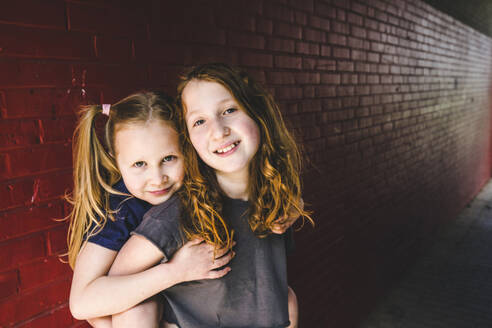 Cute girl embracing sister while standing against brick wall - IHF00342