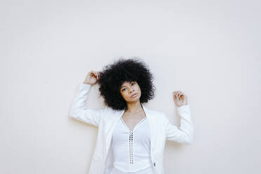Black womam, wearing white suit, leaning on white wall - TCEF00732