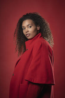 Serious young woman with curly hair wearing coat standing against red background - SNF00311