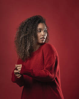 Serious thoughtful woman with curly hair standing against red background - SNF00314