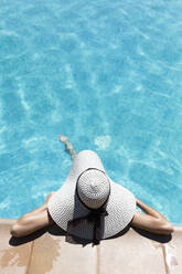 Young woman wearing hat relaxing in swimming pool at tourist resort during sunny day - JPTF00548