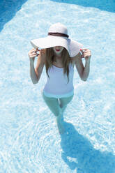 Young woman wearing hat swimming in pool at tourist resort during sunny day - JPTF00551