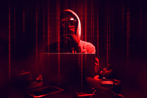 Digital Composite Image Of Male Hacker Using Laptop With Binary Codes In Darkroom - EYF05262