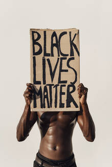 Man holding Black Lives Matter sign in front of his face - EGAF00156