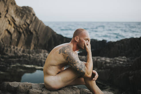 Spain, Andalusia, Almeria, artistic male nude on volcanic rocks by the sea - MIMFF00052