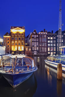 Netherlands, North Holland, Amsterdam, Tourboats moored in old town harbor at night - ABOF00523
