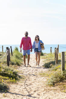 Happy couple with sunglasses holding hands while walking on beach - CAVF84997