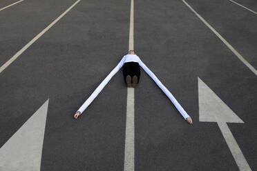 Woman with long artificial hands lying amidst arrow symbols on road - PSTF00766