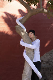 Relaxed woman with artificial long hands embracing tree trunk against wall - PSTF00772