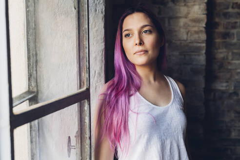 Portrait of a stylish young woman with pink hair in loft - MEUF00680