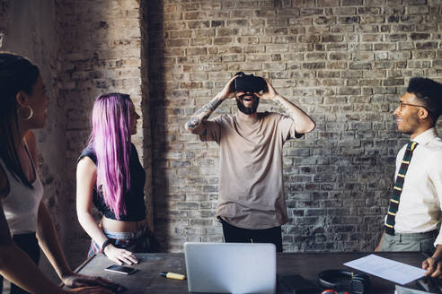 Creative team using Vr goggles in loft office - MEUF00719