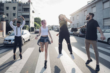 Group of carefree friends jumping on a street in the city - MEUF00785