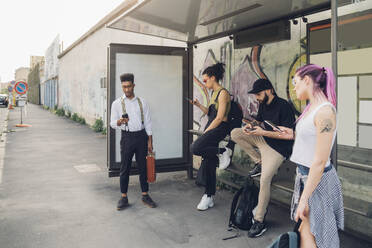 Group of friends using smartphones at bus stop in the city - MEUF00791