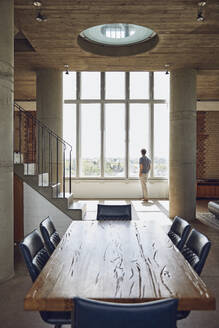 Wooden table in a loft flat with man at the window in background - MCF00933