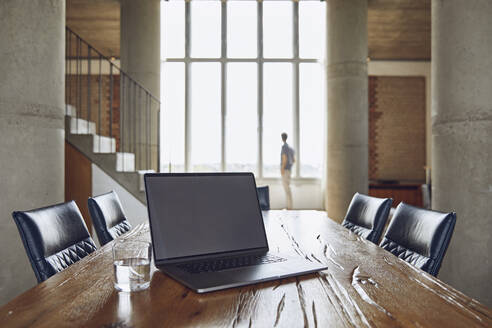 Laptop on wooden table in a loft flat with man at the window in background - MCF00936