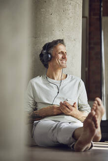 Smiling senior man with headphones listening music in a loft flat - MCF00978