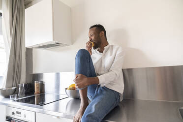 Laughing man sitting on kitchen counter at home eating an apple - AHSF02746