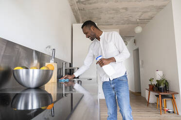 Smiling man standing in kitchen of his apartment cleaning countertop - AHSF02755